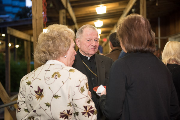 Archbishop Gregory Aymond visits with guests.